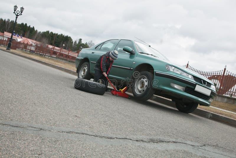 Boy Helps Change Car Tire Stock Photos