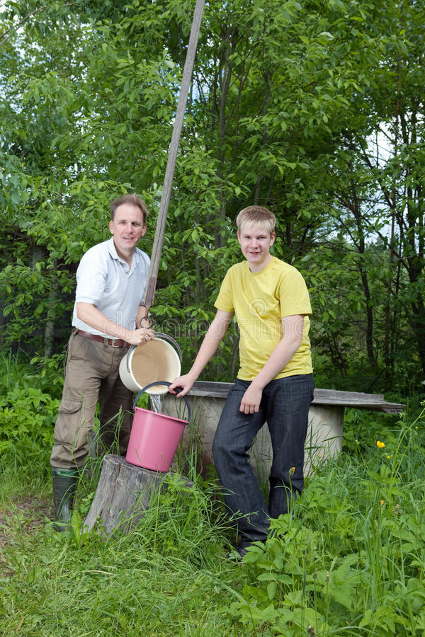 The Boy Helps The Father To Pour Water In A Bucket Stock Photos
