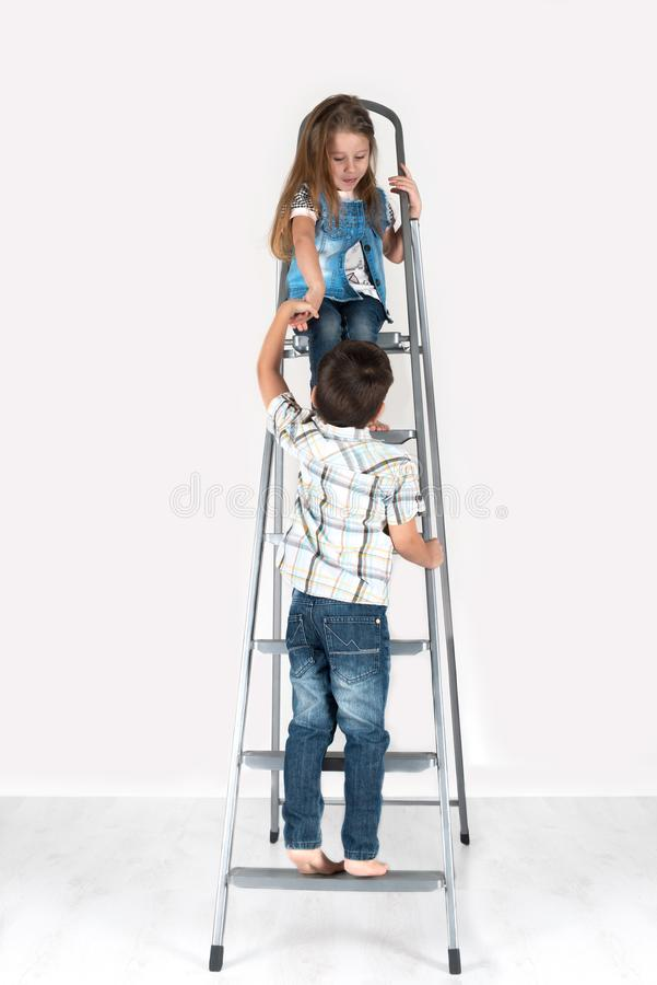 The boy helps the girl to go down on a ladder. The boy helps the girl to go down on a short flight of stairs stock images