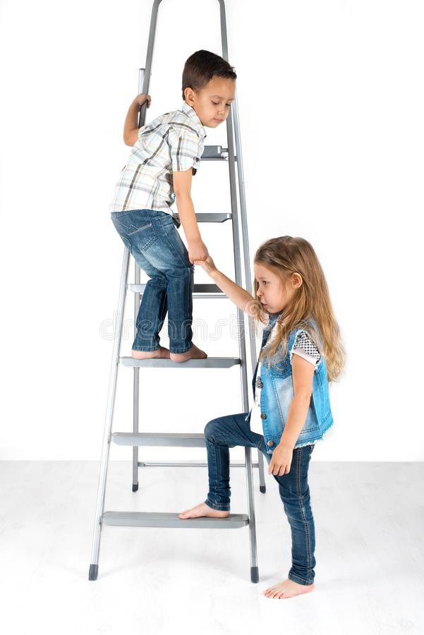 The boy helps the girl to rise on a ladder. The boy helps the girl to rise on a short flight of stairs royalty free stock image