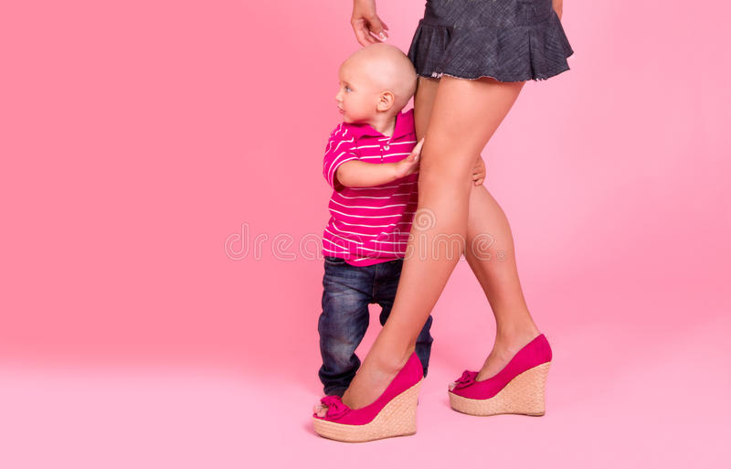 Download Boy hides behind mom feet stock image. Image of studio - 26719867