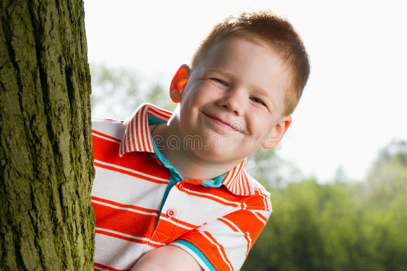 Download Boy hiding behind tree stock photo. Image of grinning - 24613212
