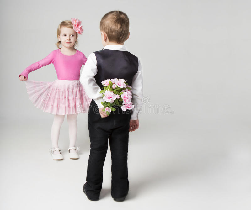 Boy hiding and going to give a girl a bouquet. Girl is flirting. Studio shot. Gray background. Sweet relationship stock image