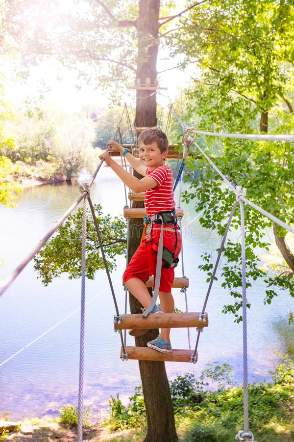 Boy and high tree rope bridge in adventure park royalty free stock image