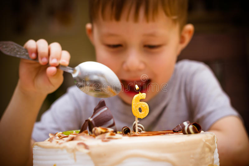Boy in his birthday. The boy looks at the birthday cake royalty free stock photo