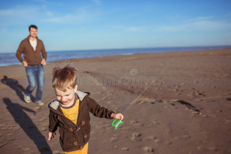 A boy and his dad are running on the sand stock photography