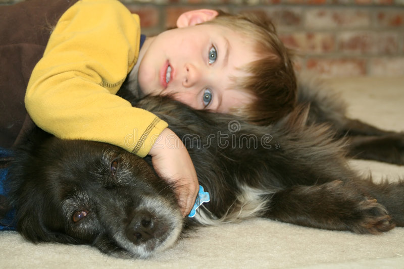 Boy and His Dog. A young boy rests his head on his favorite pet