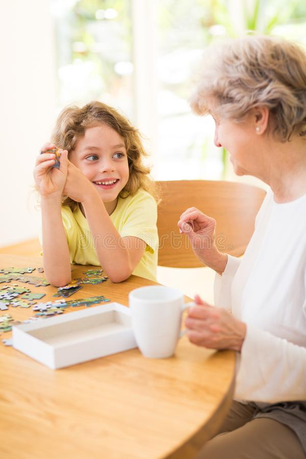 Boy and his grandmother assembling the puzzle together royalty free stock images