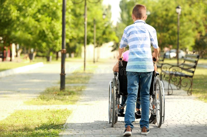 Boy and his handicapped sister resting in park stock photos