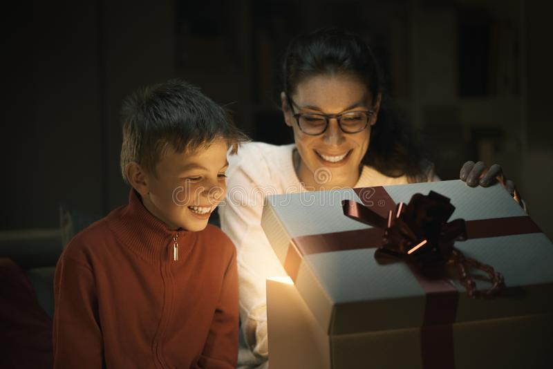 Boy and his mom opening a beautiful Christmas gift stock images