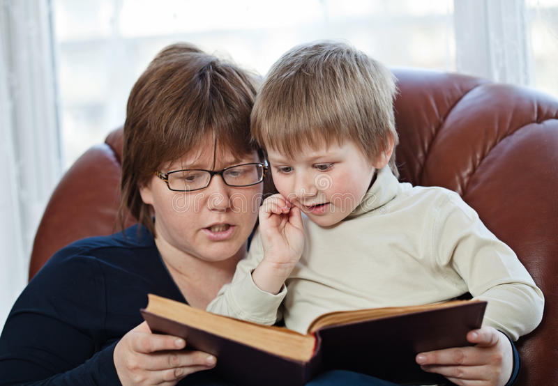 Boy and his mom reading book together royalty free stock photography