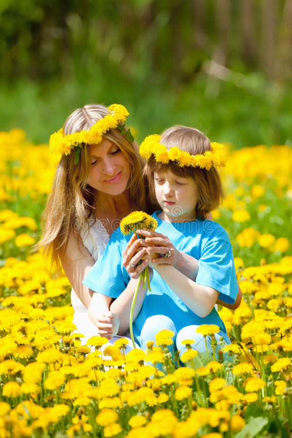 Boy and his Mother Sitting in a Dandelion Field stock photos