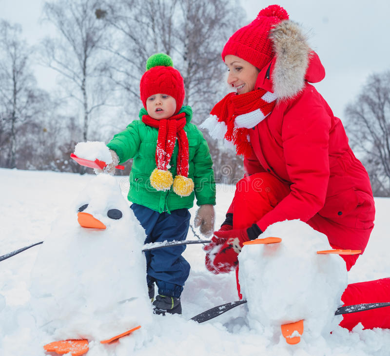 Boy and his mother with a snowman stock image