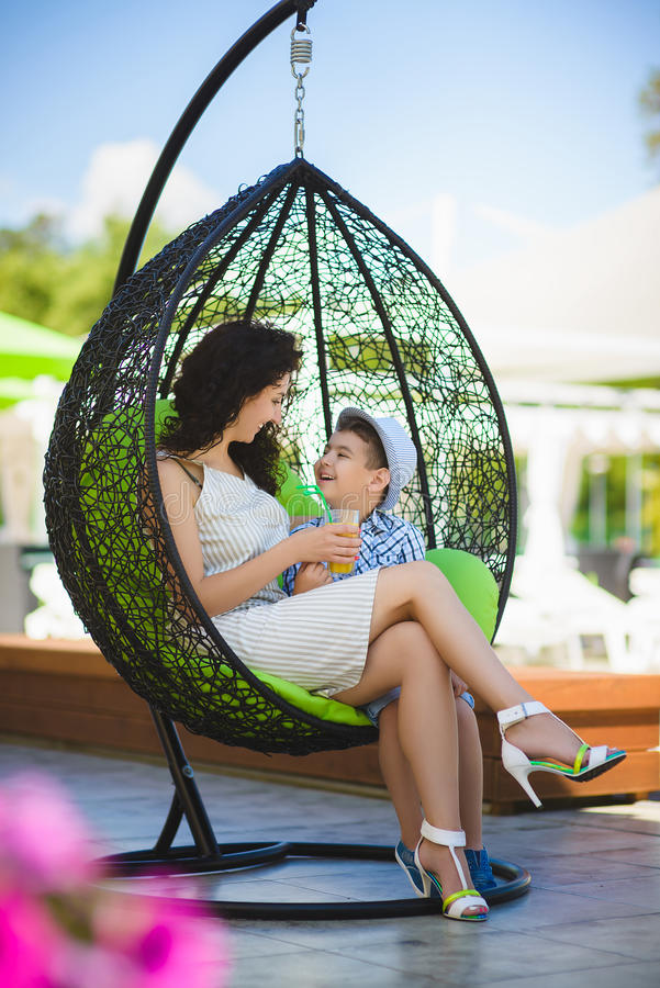 Boy and his mother tasting dessert with juice in resort restaurant outdoor stock image
