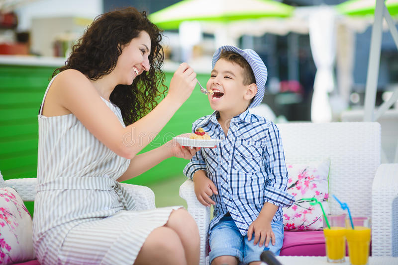 Boy and his mother tasting dessert with juice in resort restaurant outdoor royalty free stock photo