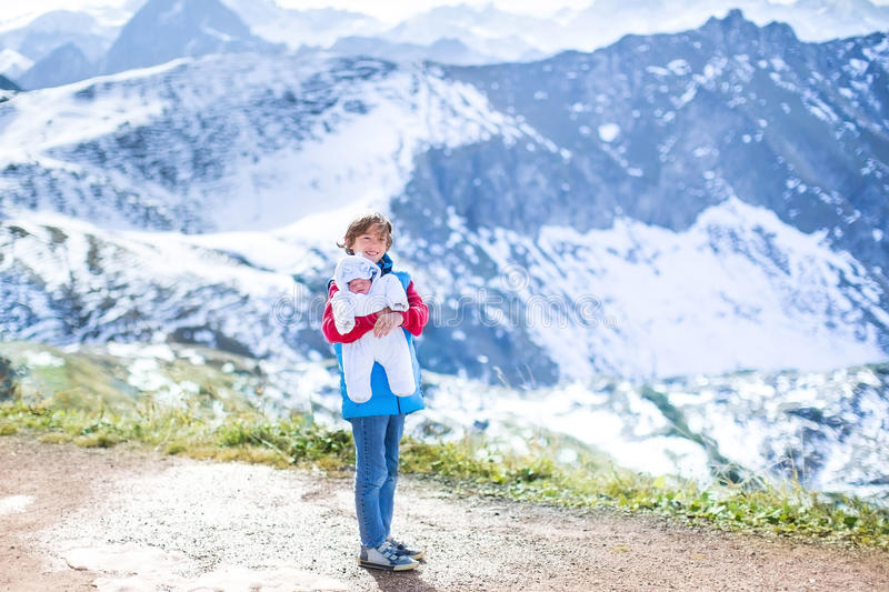 Boy With His Newborn Baby Brother In Mountains Stock Photo