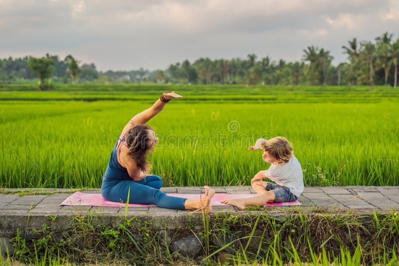 Boy and his yoga teacher doing yoga in a rice field royalty free stock photo