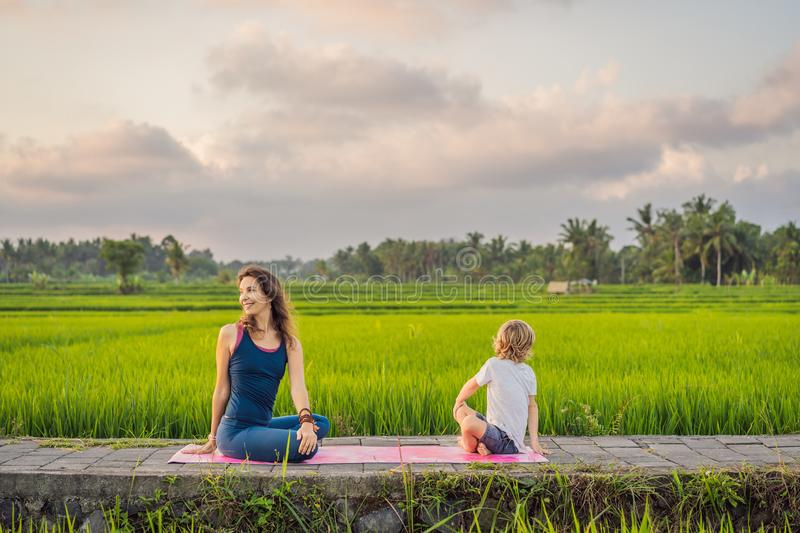 Boy and his yoga teacher doing yoga in a rice field.  stock images