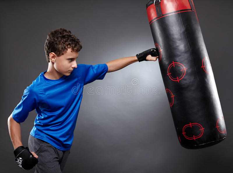 Boy hitting the punching bag. On gray background royalty free stock photography