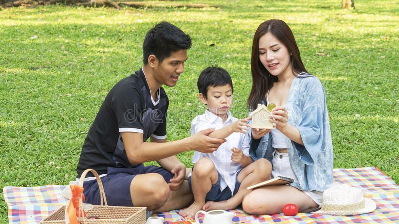boy hold money saving house box with mother and father in park.Happy family picnic concept. royalty free stock image