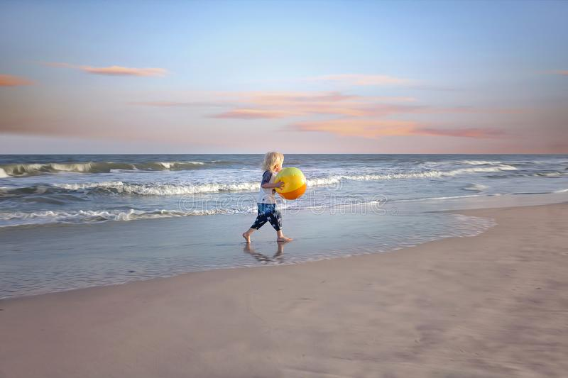 Boy Holding Ball Near Body of Water royalty free stock photography
