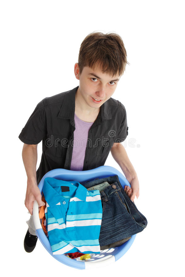 Boy holding a basket of clothes. Teenage boy holding a basket of clothes royalty free stock photography