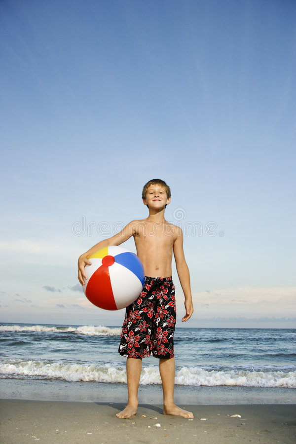 Boy holding beachball on beach. royalty free stock photography