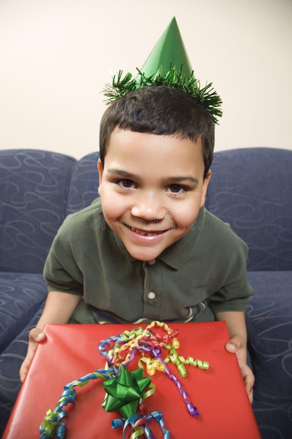 Boy holding birthday present. stock images