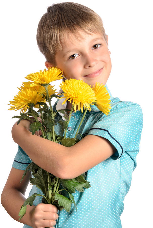 Boy holding a bouquet of chrysanthemums. Smiling and looking at the camera royalty free stock image