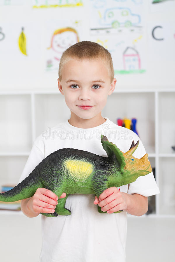 Boy holding dinosaur. Portrait of a happy european blond boy holding a toy dinosaur in classroom stock photos