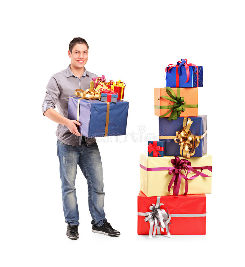 Download Boy Holding A Gift Next To A Pile Of Gifts Royalty Free Stock Photography - Image: 22279197