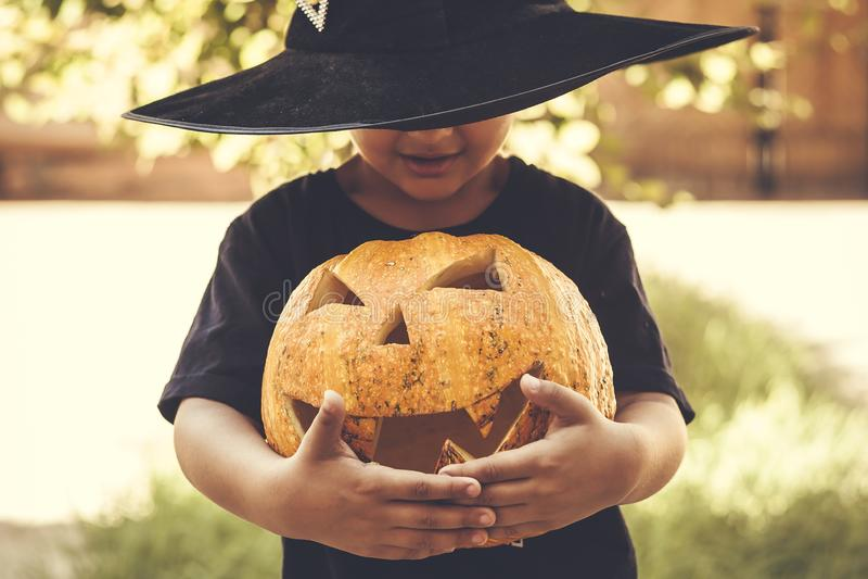 Boy holding halloween pumpkin. Halloween 2019. Little boy holding carved Halloween pumpkin - Jack O`Lanterns at outdoors. Family preparations to Halloween stock photo