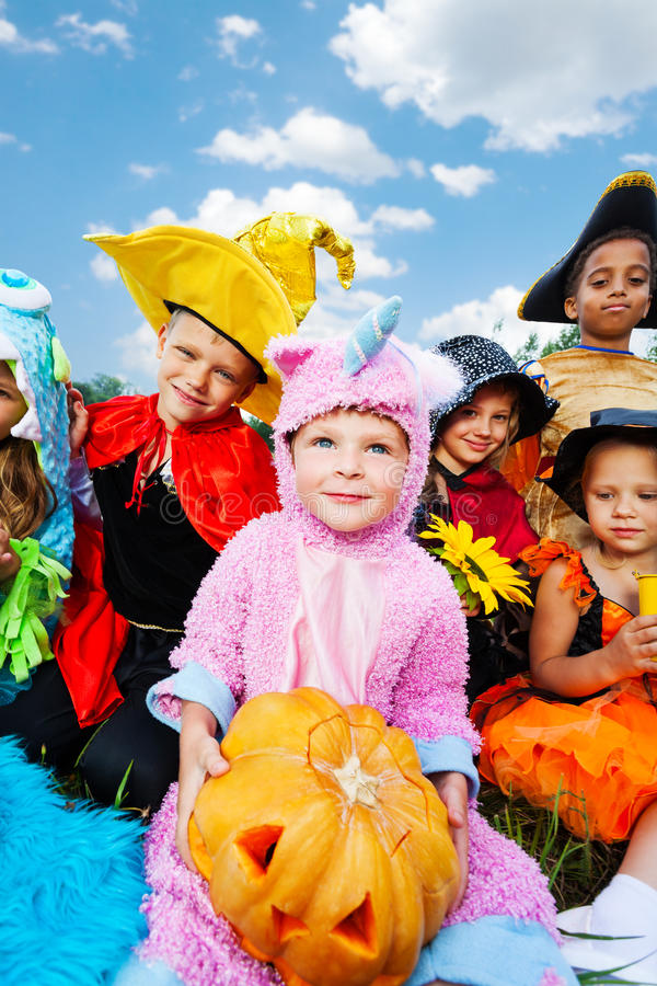 Boy holding Halloween pumpkin with his friends stock photo