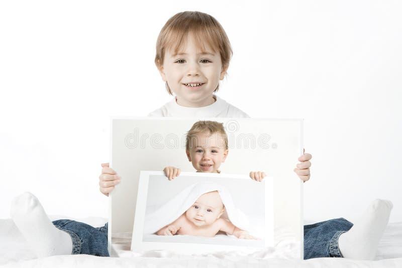 Boy holding his baby photos royalty free stock photo