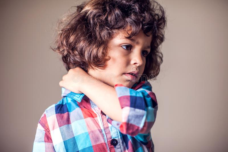 A boy holding his painful neck. Children, healthcare and medicine concept. A boy holding his painful neck. Children, healthcare, medicine concept royalty free stock image