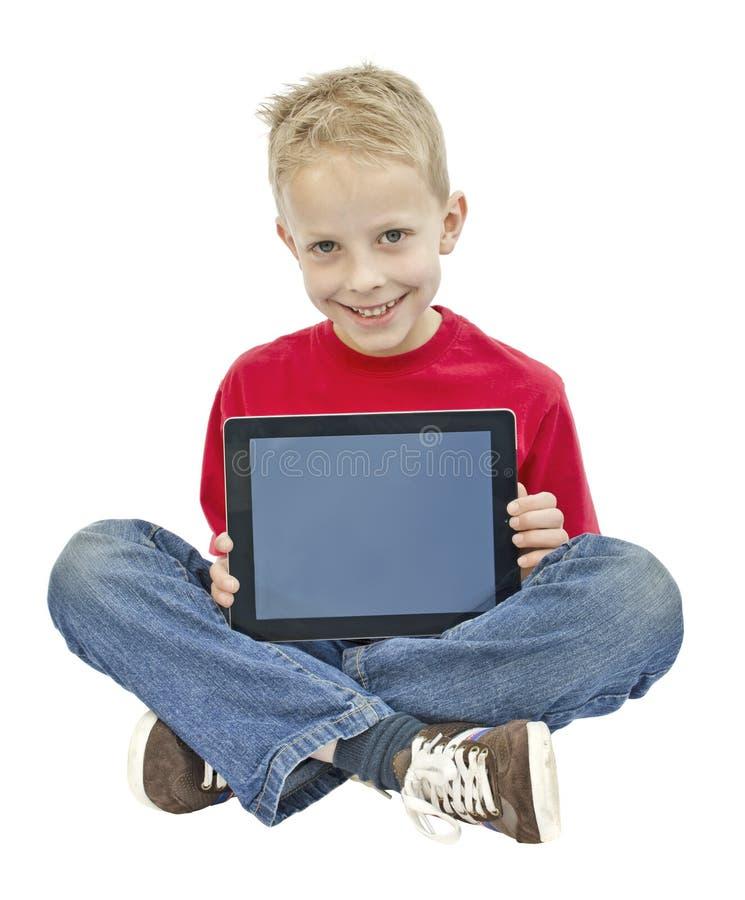 Boy holding ipad. Young boy showing an ipad