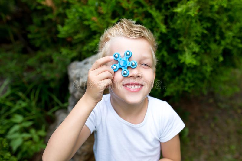 Boy with spinner. The boy is holding new fashionable toy fidget-spinner, hand-spinner royalty free stock photos