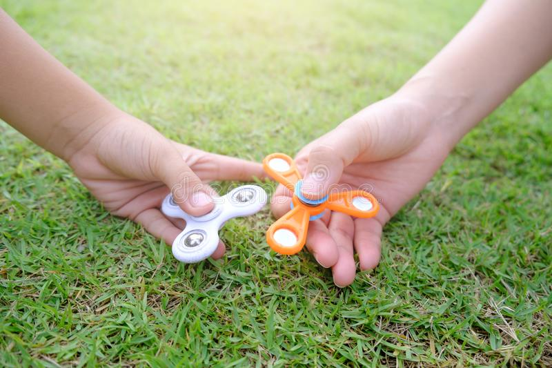 Boy holding play two fidget spinners, Fidget spinner white and o stock image