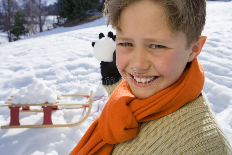 Boy (7-9) holding snow ball in snow field, smiling, portrait, close-up, sled in background stock photography