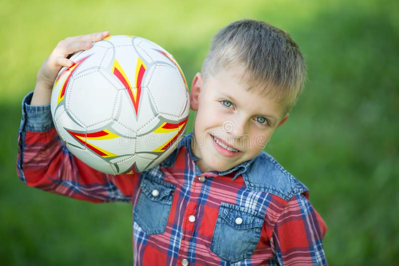 Boy holding a soccer ball in his hands. And smiling stock photography