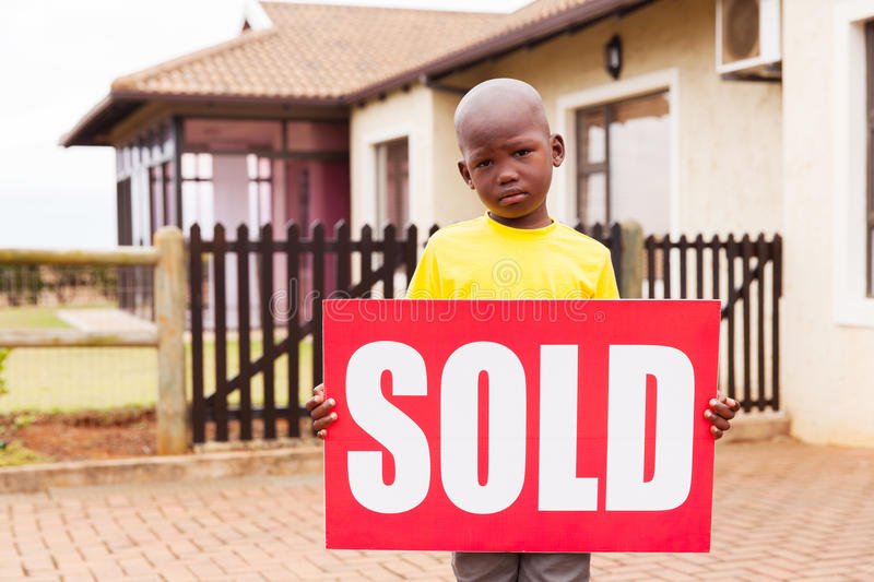 Boy holding sold sign. Little african boy standing outside the house and holding sold sign royalty free stock image