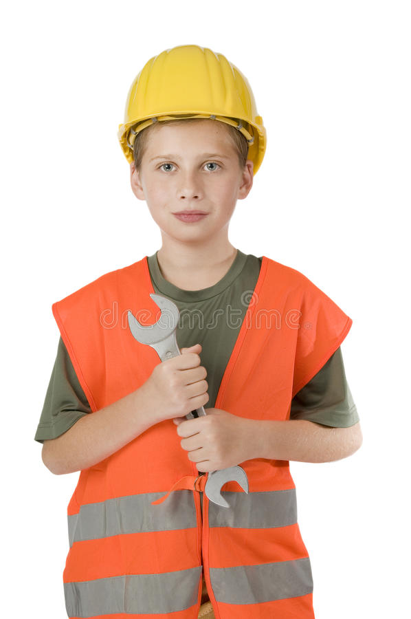 Boy holding a Spanner on white. Frontal head-and-shoulder view of a 13 year old male teenager with yellow construction helmet and orange vest against white stock photo