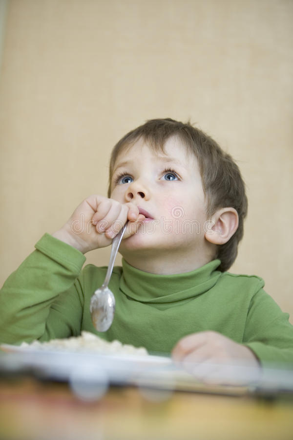 Boy Holding Spoon While Looking Up At Table royalty free stock photos