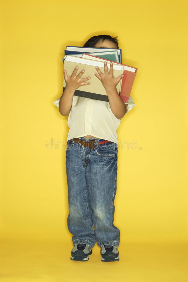 Boy holding stack of books. stock photos