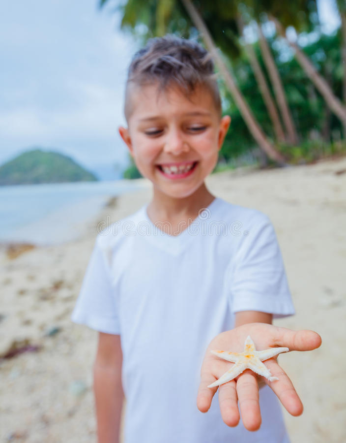 Boy holding a starfish stock photography