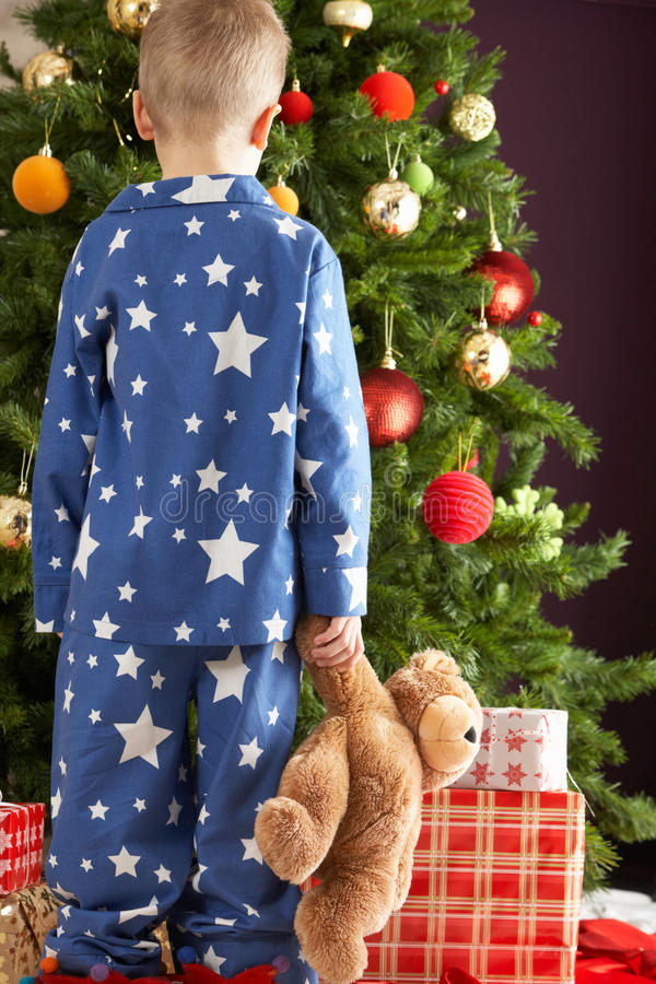 Download Boy Holding Teddy Bear In Front Of Christmas Tree Stock Photo - Image: 15376292