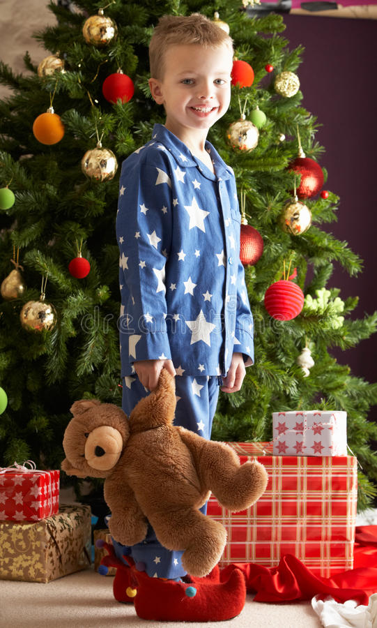Download Boy Holding Teddy Bear In Front Of Christmas Tree Royalty Free Stock Images - Image: 15376319