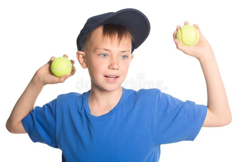 Boy holding tennis balls royalty free stock photo