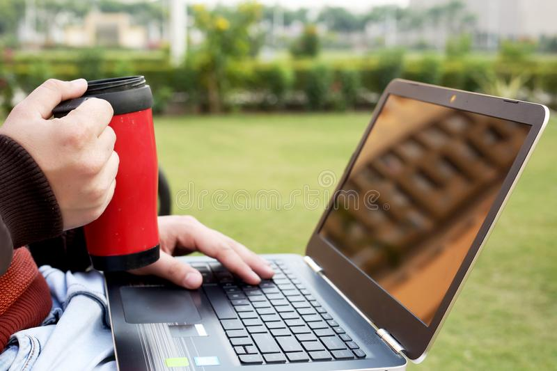 Boy is holding water bottle in hand with laptop.  stock image