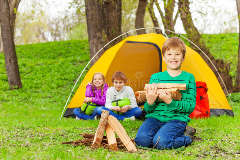 Boy holding the wood for bonfire with other kids royalty free stock photo